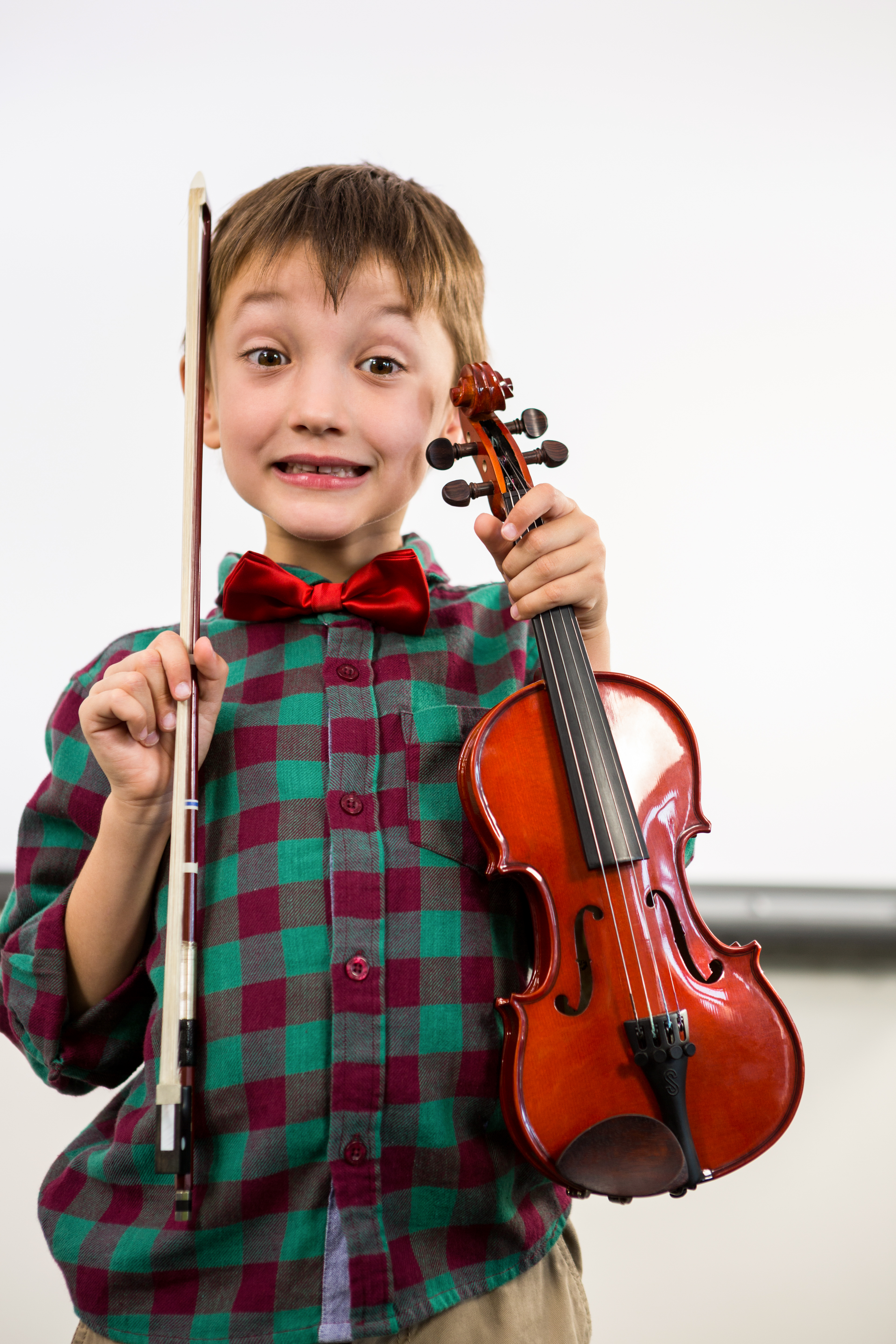 Portrait of cute boy holding violin with bow in classroom