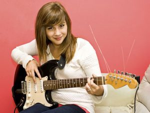 Girl playing guitar in a lesson