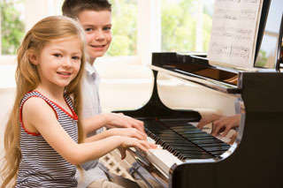 Boy and girl playing the piano